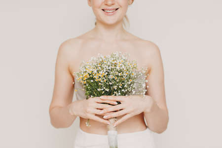 Young and beautiful blonde woman with daisies bouquet