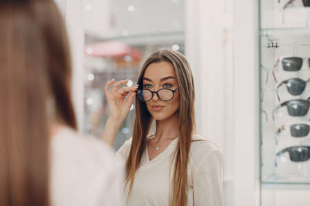 Close up of gorgeous young smiling woman smiling picking and choosing glasses at the optician corner at the shopping mall. Happy beautiful woman buying eyewear eyeglasses at the optometrist Standard-Bild