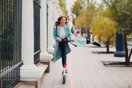 Young woman with electric scooter in blue coat at the city Standard-Bild