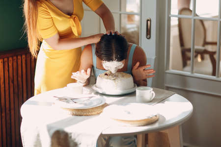 Young woman dips face in white cake with cream. Happy birthday concept.