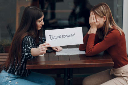 Hidden depression concept. Woman crying. Second woman holding white sheet paper labeled word Depression in hand. Two women talking in street cafe. Stok Fotoğraf