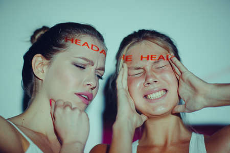 Young adult women holds hands on head ad having suffering facial expressions with word Headache on her face Stok Fotoğraf