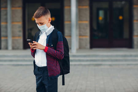 Schoolboy young boy with mobile phone and medical face mask standing at school on background Stok Fotoğraf