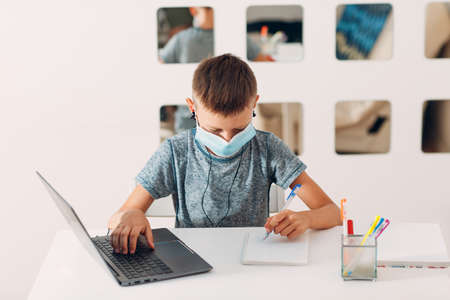 Young boy in headset sitting at table with laptop and medical face mask and preparing to school. Online education concept. Stok Fotoğraf