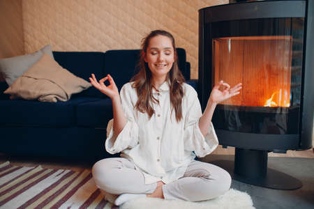 Portrait of young woman sitting in lotus position indoors with fireplace. Yoga and meditation zen like concept.