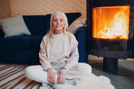 Mature gray haired woman sitting on sofa in living room with fireplace