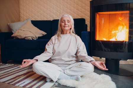 Portrait of senior woman sitting in lotus position indoors with fireplace. Yoga and meditation zen like concept. Stok Fotoğraf