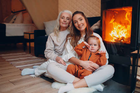 Mother and child sitting and playing on sofa near fireplace. Mom and baby. Parent with daughter and grandson little kid relaxing at home. Family having fun together.