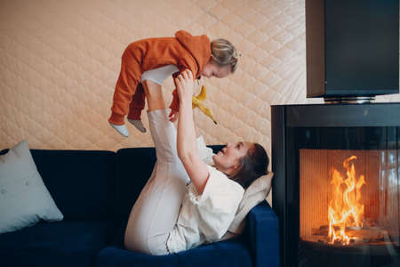Mother and child sitting and playing on sofa near fireplace. Mom and baby. Parent and little kid relaxing at home. Family having fun together.