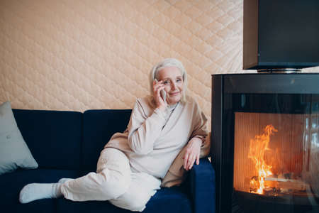 Elderly gray haired woman sitting on sofa and talking smartphone in living room with fireplace