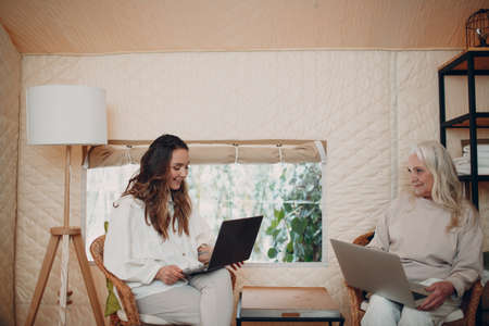 Women with laptop relaxing at glamping camping tent. Modern vacation lifestyle concept.