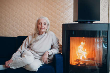 Elderly gray haired woman sitting on sofa in living room with fireplace Stok Fotoğraf