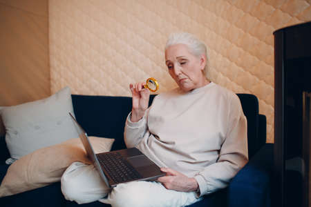 Elderly woman grandmother learns to work at home on laptop computer and internet with magnifier