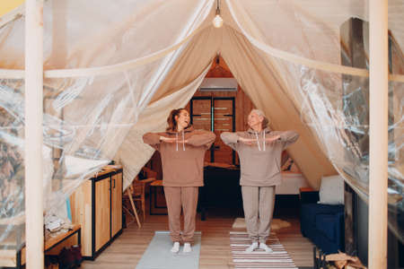Family doing exercises sports indoor. Young and senior elderly woman relaxing at glamping camping tent. Mother and daughter modern at fitness vacation lifestyle concept.