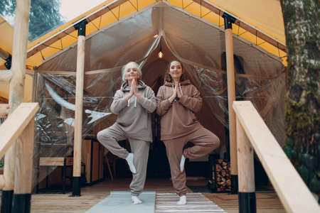 Woman senior and young relaxing at glamping camping tent. Women family elderly mother and young daughter doing yoga and meditation indoor. Modern zen-like vacation lifestyle concept. Stok Fotoğraf