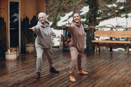 Women doing exercises sports and fitness outdoors. Young and senior elderly woman warming up and yoga at glamping. Mother and daughter having zen like modern fitness vacation.