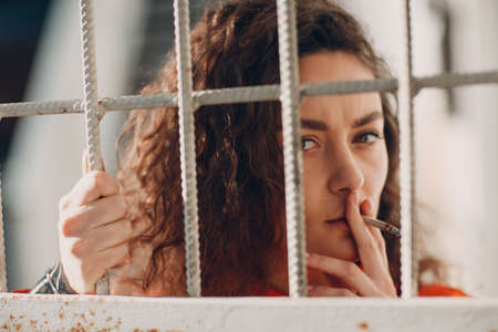 Young brunette curly woman in orange suit behind jail bars smokes cigarette. Female in colorful overalls portrait. Stok Fotoğraf