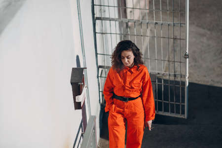 Young prisoner woman in orange suit at jail smoking. Female in colorful overalls portrait. Stok Fotoğraf