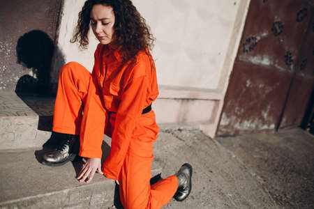 Young brunette curly woman in orange suit. Female in colorful overalls portrait.