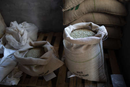Green coffee beans in burlap sack at roaster company