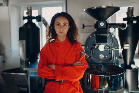 Young woman worker with hammer in orange suit in workshop with Coffee roaster machine during coffee roasting process Stok Fotoğraf