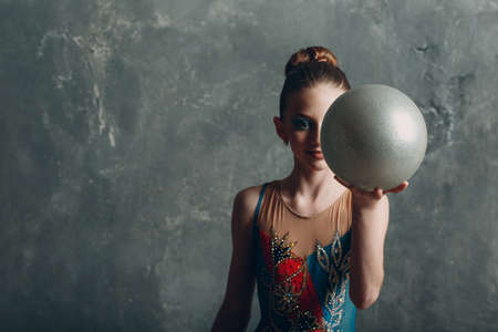 Young girl professional gymnast woman portrait rhythmic gymnastics with ball at studio