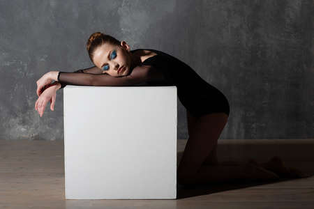 Young professional girl gymnast woman resting on white cube after training. Rhythmic gymnastics concept.