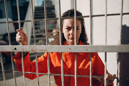 Young woman in orange suit behind jail bars. Female in colorful overalls portrait. Law and justice concept. Stok Fotoğraf