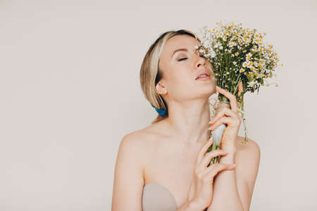 Young and beautiful blonde woman with camomile bouquet