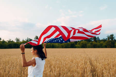 Woman with American flag in wheat field at sunset. 4th of July. Independence Day and Harvesting Concept.