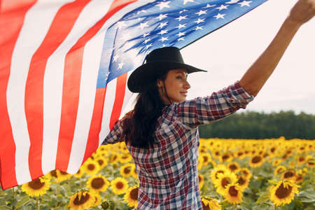 Young woman with American flag in the sunflower field. Harvest USA concept.