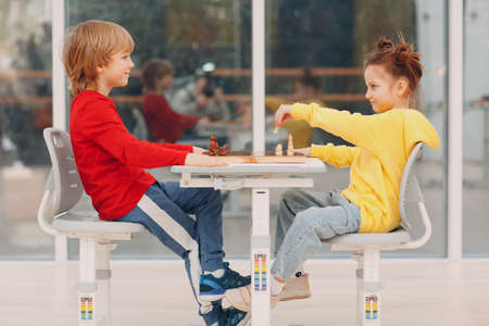 Little couple kids playing chess at kindergarten or elementary school Foto de archivo