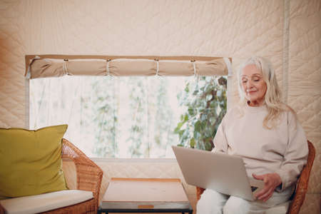 Mature Woman with laptop relaxing at glamping camping tent. Modern vacation lifestyle concept.