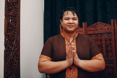Thai man smiling portrait with traditional Thai suit and welcome pray gesture folded hands Foto de archivo