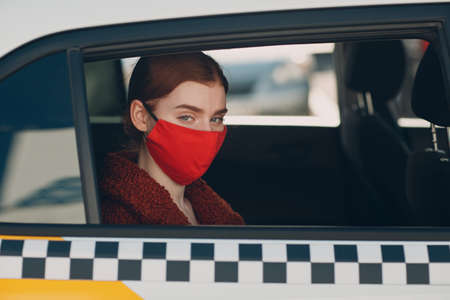 Young woman passenger takes a ride by taxi car during the pandemic quarantine. Woman wearing sterile medical face mask. Social distance and health safety in transportation concept.