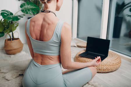 Adult mature woman doing yoga at home living room with online tutorials on laptop