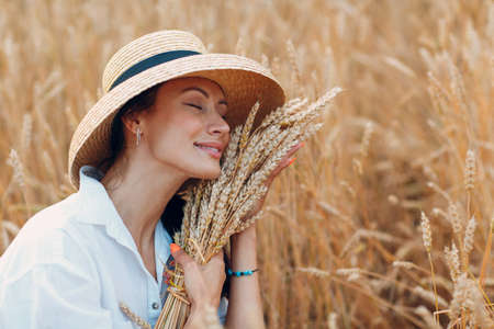 Young Woman in straw hat holding sheaf of wheat ears at agricultural field