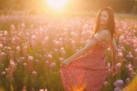Girl on blooming Sally flower field at sunset. Lilac flowers and woman.