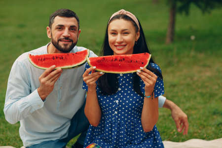 Young adult woman and man couple picnic at green grass meadow in park having fun and smile with watermelon Foto de archivo