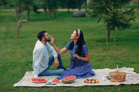 Young adult woman and man couple picnic at green grass meadow in park Foto de archivo
