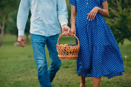 Happy Couple with Fruits in Picnic Basket Walking in the Park. Foto de archivo