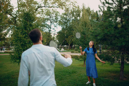 Young adult couple playing badminton in the park