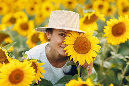 Beautiful smiling young woman in a hat with flower on her eye and face on a field of sunflowers Foto de archivo
