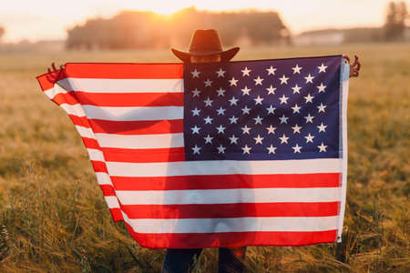 Woman farmer in the agricultural field with american flag on sunset