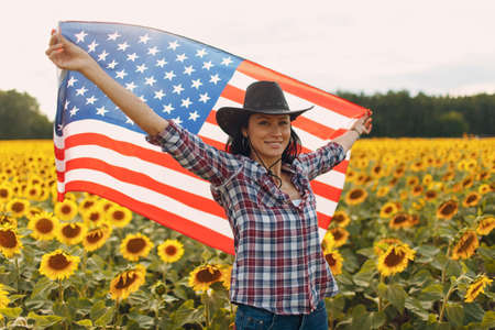 Young smiling woman with American flag in the sunflower field. 4th of July Independence Day USA concept.