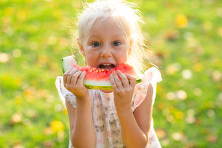 Cute blond little girl eating watermelon on the grass in park
