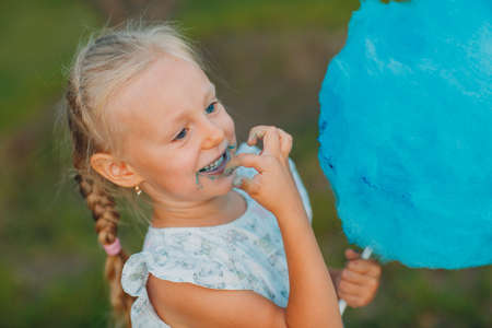 Little blond girl eating blue cotton candy in the park.