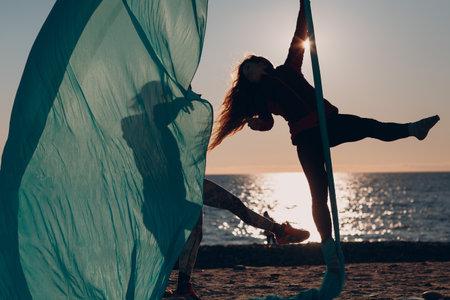 Aerial yoga on the beach. Healthy Woman.