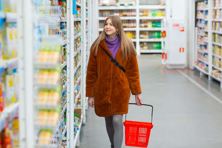 Young smiling woman with a grocery basket and shelves with groceries in a store. Foto de archivo