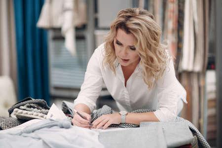 Interior designer woman at work. Design and interior decoration with fabric. Foto de archivo